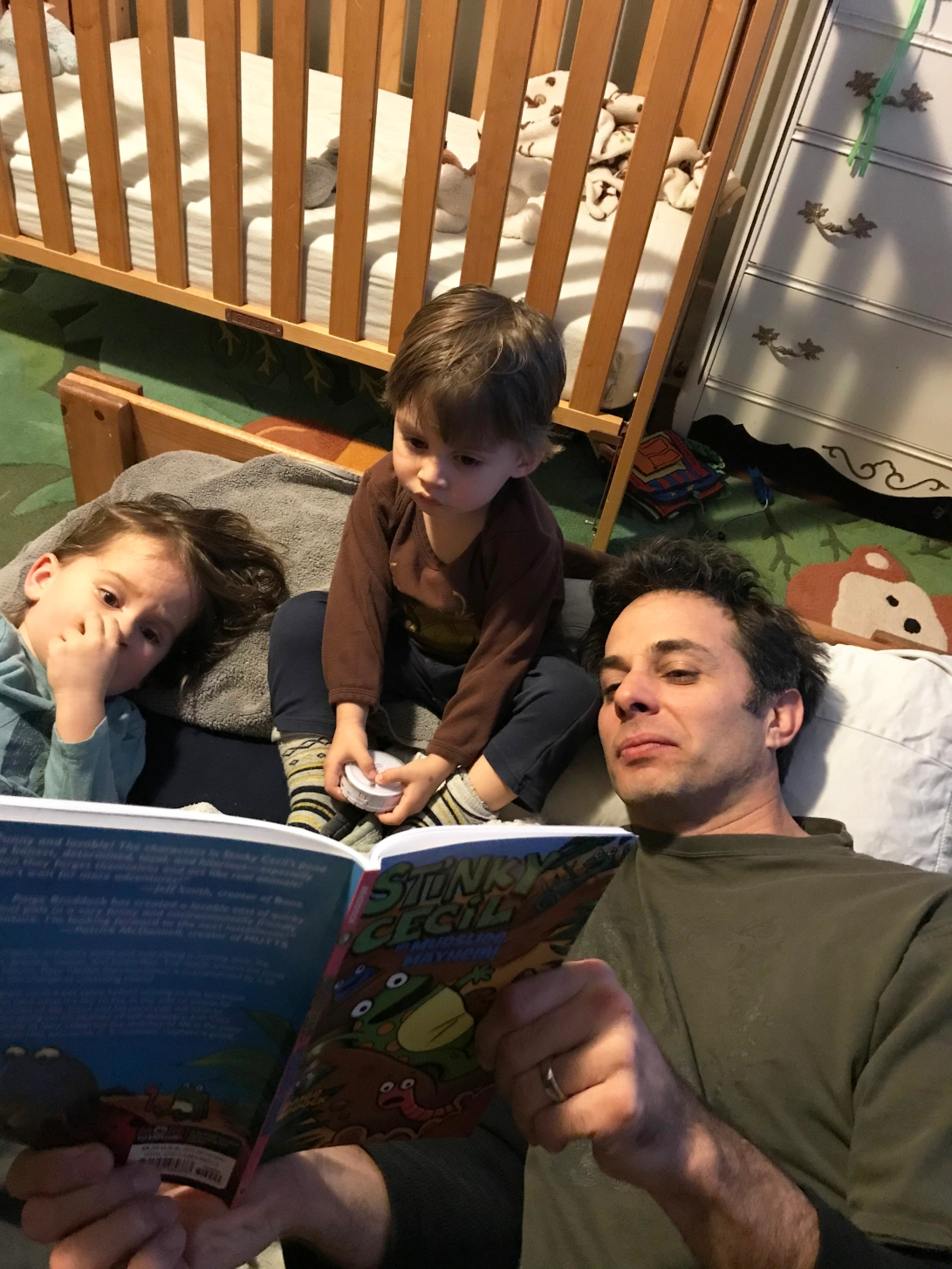 Photo of Dad with two sons reading Mudslide Mayhem